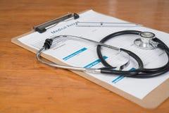 在剪贴板的病历有在书桌上的听诊器的 免版税库存图片