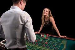在副主持人背面的一个绿色赌博娱乐场桌的特写镜头一件白色衬衣的,图象与轮盘赌的和芯片,富有 免版税库存照片