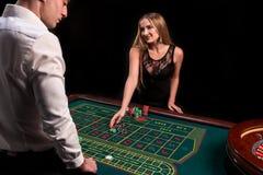在副主持人背面的一个绿色赌博娱乐场桌的特写镜头一件白色衬衣的,图象与轮盘赌的和芯片,富有 免版税库存图片