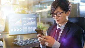 在办公室东亚商人使用智能手机,键入淘气鬼 免版税库存图片