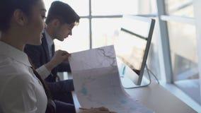 在办公室两青年人与在纸的图表一起使用在计算机前面 4K 影视素材