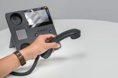 在办公室供以人员IP电话举行耳机要求事务 免版税库存图片