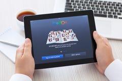 在办公室供以人员拿着与app Badoo的iPad在屏幕上 免版税库存图片