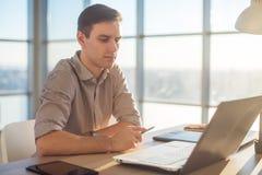 在办公室供以人员研究便携式计算机的自由职业者商人 免版税库存照片