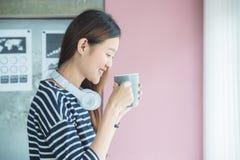 在办公室和微笑的妇女饮用的咖啡 免版税库存图片