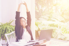 在办公室在工作以后艰苦放松和自由概念举的女商人胳膊 免版税图库摄影