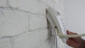 在办公室室里面的人使用在墙壁上固定的一个输送路线打打电话 股票录像