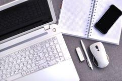在办公室工作场所上看法的上流有手机和膝上型计算机接近的键盘和老鼠的与笔记本、笔和usb 免版税库存图片