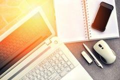 在办公室工作场所上看法的上流有手机和膝上型计算机接近的键盘和老鼠的与笔记本、笔和usb 免版税图库摄影