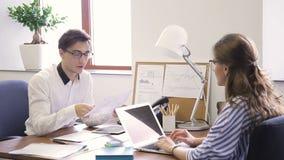 在办公室年轻人问对妇女的文件的问题在对面 股票视频