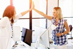 在办公室庆祝成功的两个少妇 免版税库存图片