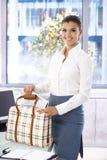 在办公室微笑的美好的女实业家包装 免版税图库摄影