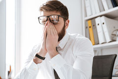 在办公室感人的眼睛的紧张商人 免版税图库摄影
