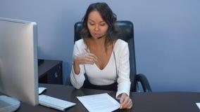 在办公室支持耳机的电话操作员与膝上型计算机一起使用 库存照片