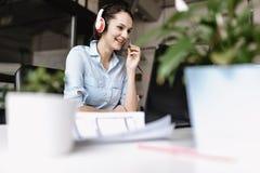 在办公室样式衣裳打扮的年轻深色的妇女与顾客谈话通过坐在书桌的耳机与 免版税库存图片