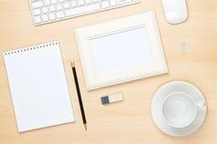 在办公室桌上的照片框架与笔记薄、计算机和咖啡古芝 免版税图库摄影