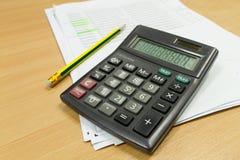 在办公室桌上的计算器和纸板料 免版税库存图片