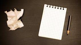 在办公室桌是笔记本、铅笔和被弄皱的板料 库存照片