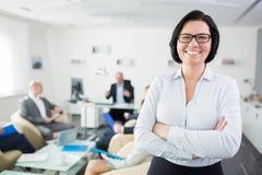 在办公室横渡的微笑的女实业家常设胳膊 免版税库存图片