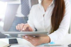 在办公室特写镜头的女性胳膊举行和用途平板电脑 免版税图库摄影
