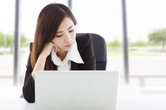 在办公室用尽和不耐烦的年轻女商人 免版税库存图片