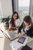 在办公室的两个微笑的女性同事坐在书桌使用膝上型计算机和片剂个人计算机 库存照片