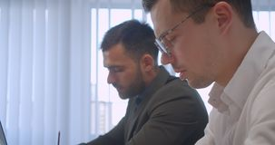在办公室的两个成人白种人商人特写镜头画象户内 一台使用的膝上型计算机另一采取 影视素材