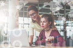 在办公室的两名年轻女实业家 一个女孩坐在膝上型计算机前面的桌上 免版税库存图片