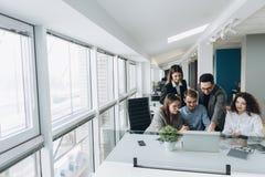 在办公室的小组微笑的被鼓舞的年轻商人 免版税库存图片