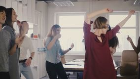 在办公室聚会的愉快的欧洲妇女领导跳舞 不同种族的同事一起享受乐趣接合时间活动4K 股票录像