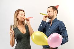 在办公室衣裳的年轻滑稽的夫妇庆祝一个生日或公司事件,组织一个党用香槟,气球 图库摄影