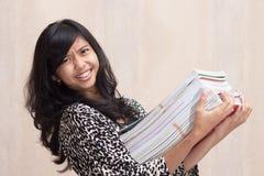 表达亚裔的学生拿着巨额书和真正地重 库存照片