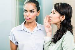 在办公室,妇女说闲话耳语在耳朵 免版税库存图片