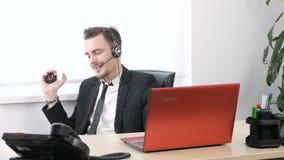 在办公室,衣服挤压手扩展器的人解决,当坐在办公室和发表演讲关于耳机时 股票录像