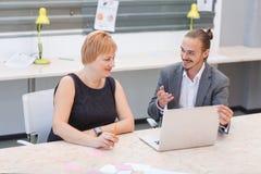 在办公室 两名工作者谈论某事,当坐在膝上型计算机时 库存图片