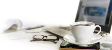 在办公桌上的咖啡杯有手机的,膝上型计算机的玻璃 免版税库存照片