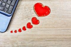 在办公桌上的红色心脏被连接到计算机 概念:华伦泰` s天,消息,在社会网络的书信 库存图片