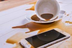 在办公桌上,咖啡在电话溢出了 免版税图库摄影