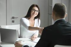 在办公桌的商人和女实业家握手 图库摄影