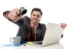 在办公桌的商人研究计算机膝上型计算机指向枪的看起来恼怒和疯狂 免版税图库摄影