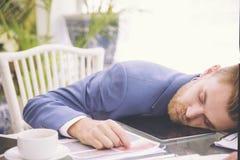 在办公桌的商人重的工作量睡眠有财务板料计算器和咖啡的 劳累过度的概念 库存照片