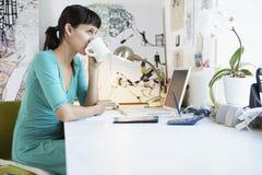 在办公桌的女实业家饮用的咖啡 库存照片