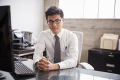 在办公桌的年轻亚洲商人,看对照相机 库存图片