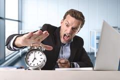 在办公桌的恼怒的被剥削的商人注重和挫败与计算机膝上型计算机和闹钟 库存照片