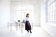 在办公桌的有吸引力的年轻创造性的妇女身分和周道看 库存照片