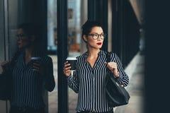 在办公楼之外的女实业家用咖啡 免版税库存图片