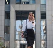 在办公楼前面的年轻女商人讲话由她的手机 图库摄影