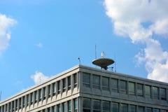 在办公楼屋顶顶部的大卫星盘 免版税库存图片