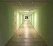 在办公楼的现代内部 有遥远的门和办公室入口的长的空的大厅 免版税库存图片