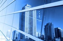 在办公楼窗口反映的大厦  免版税库存照片